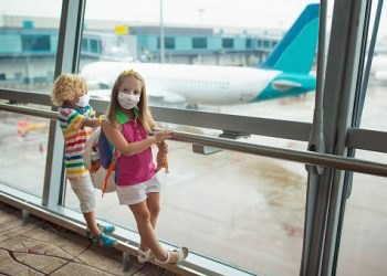 Kids at airport in face mask. Children look at airplane after coronavirus outbreak. Safe travel and flying with child in virus pandemic. Family at departure gate. Vacation after covid-19 lockdown.